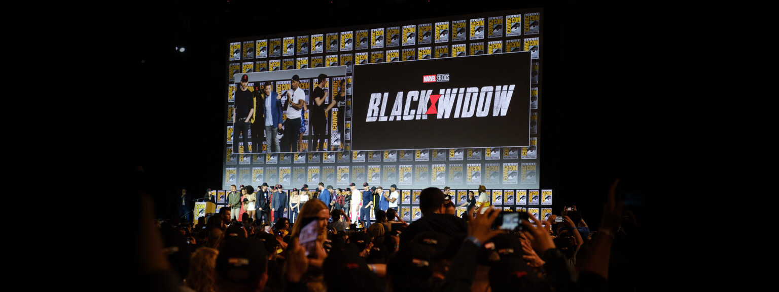 A large crowd at a convention, with the cast of an upcoming blockbuster movie onstage