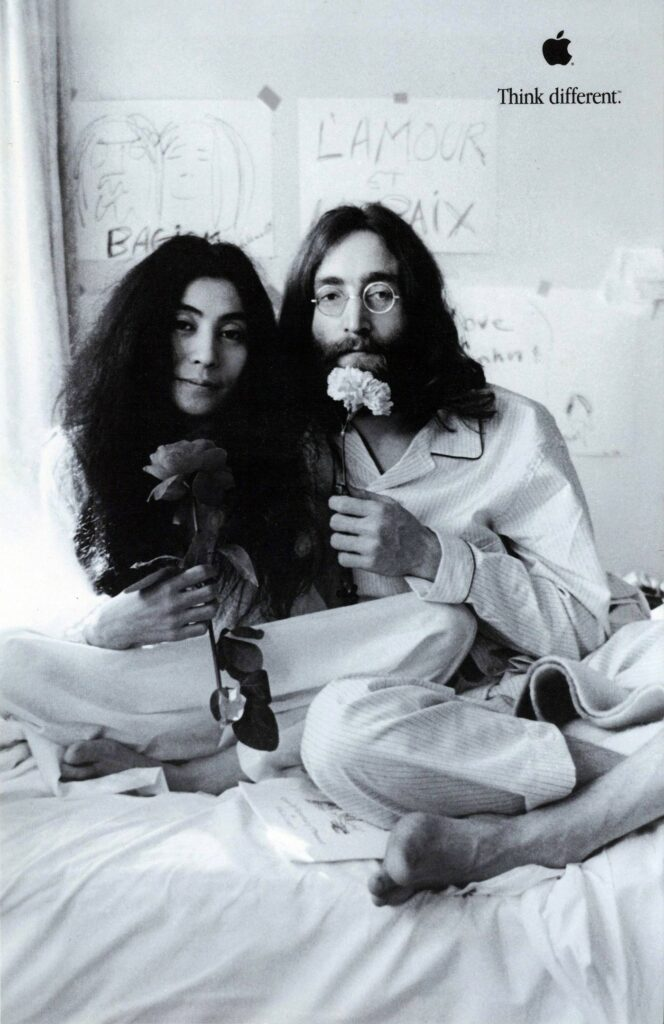 A man and a woman in their pajamas are sitting in bed holding up flowers as a gesture of peace
