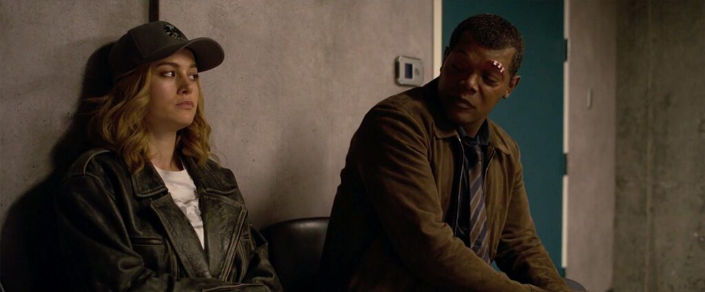 A woman (Captain Marvel) and a man (Nick Fury) sit and have a discussion