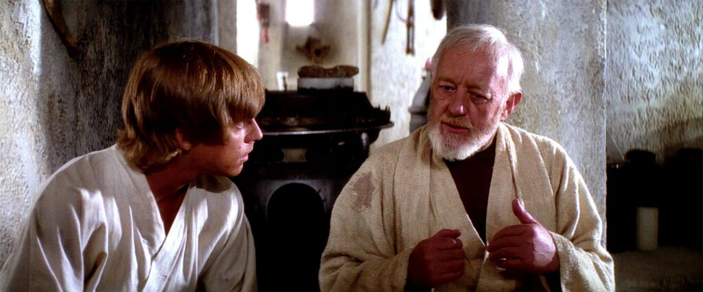 A young man (Luke Skywalker) and an older man (Obi Wan Kenobi) are sitting and having a discussion