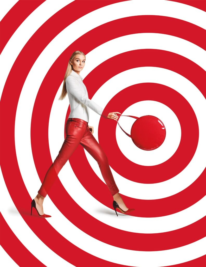Advertisement showing a woman walking and carrying a handbag. She is against a red and white bullseye.
